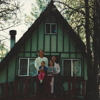 A family in front of a cabin
